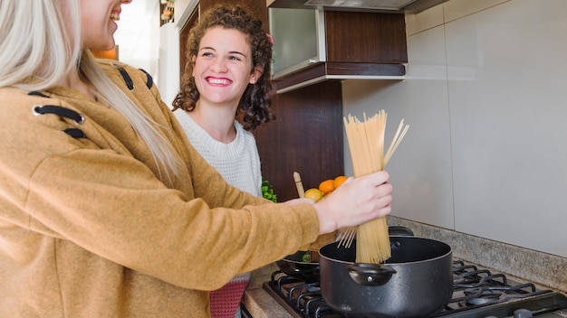 Smiling young woman cooking spaghetti in the saucepan