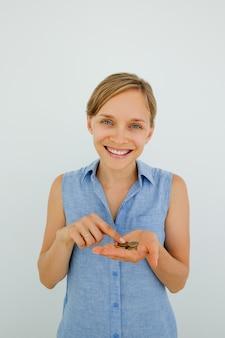 Улыбающаяся молодая женщина, подсчет монет на palm
