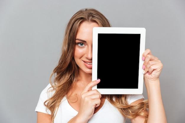 笑顔の若い女性は灰色の壁に分離された空白の画面のタブレットコンピューターで彼女の顔を覆います