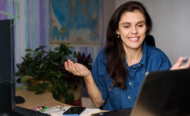 Smiling young woman in denim shirt working home near laptop