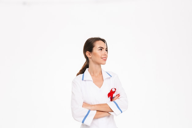 Smiling young woman doctor wearing uniform with a red ribbon standing isolated over white wall