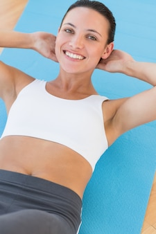 Smiling young woman doing abdominal crunches