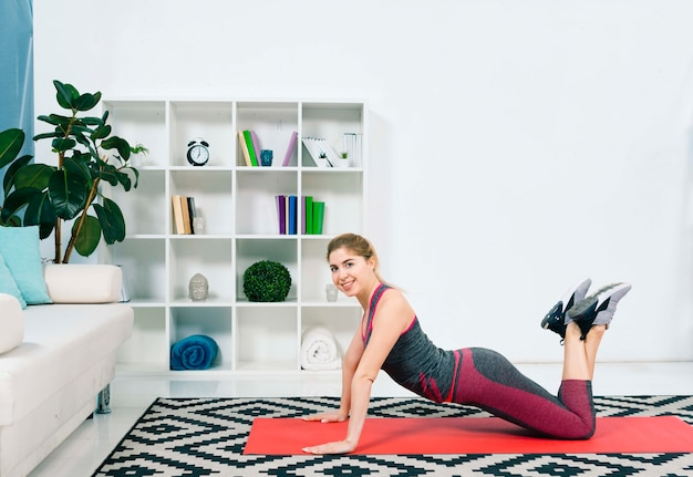 Smiling young woman doing exercise in the modern living room