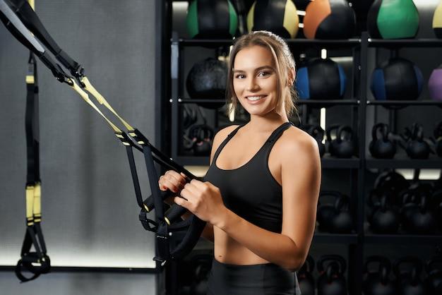 Улыбающаяся молодая женщина делает упражнения с системой trx