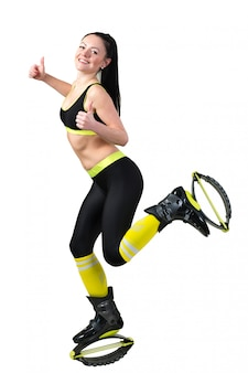 Smiling young woman doing exercises in kangoo jumps shoes
