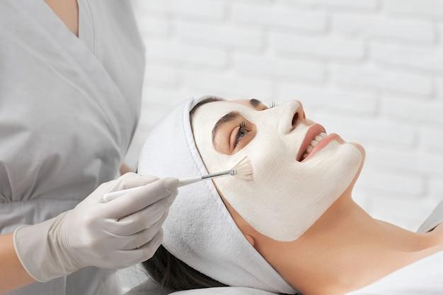 Улыбающаяся молодая женщина делает процедуру для лица в косметологе