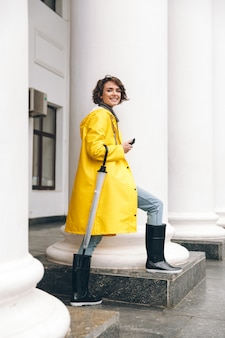 Smiling young woman dressed in raincoat.