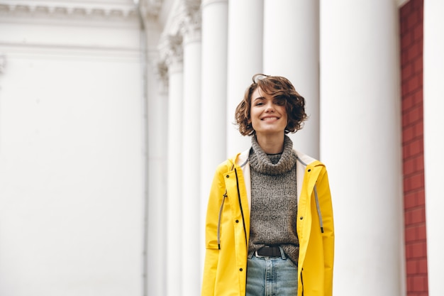 Smiling young woman dressed in raincoat