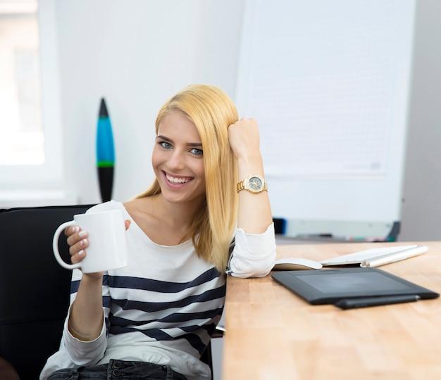 Улыбающаяся молодая женщина пьет кофе в офисе