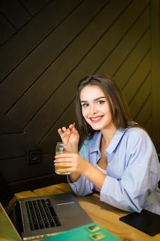 Улыбающаяся молодая женщина пьет холодный напиток в кафе с ноутбуком