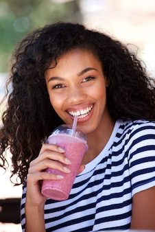 Smiling young woman drinking smoothie outside