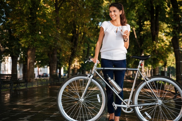 Smiling young woman drinking takeaway coffee and holding bicycle in the city park