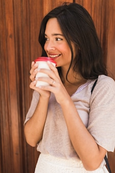 Smiling young woman drinking takeaway coffee