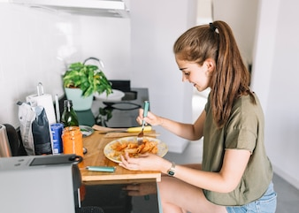 Smiling young woman eating pasta in breakfast