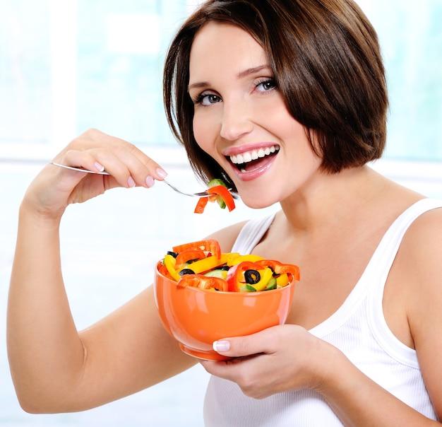 笑顔の若い女性がサラダを食べる