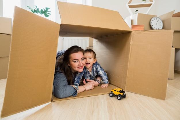 Улыбается молодая женщина, обнимая своего маленького сына в движущейся картонной коробке