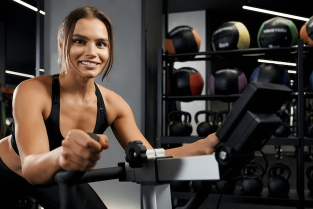 Smiling young woman engaged on exercise bike