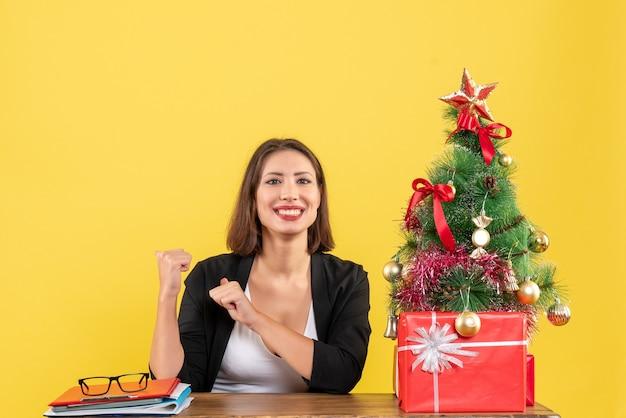 노란색에 사무실에서 장식 된 크리스마스 트리 근처 소송에서 그녀의 성공을 즐기고 웃는 젊은 여자
