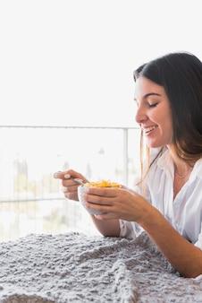 コーンフレークの朝食を楽しんでいる若い女性の笑みを浮かべてください。