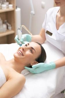 특별한 도구의 도움으로 현대 클리닉에서 피부 영양 과정을 즐기는 젊은 여성 미소 짓기