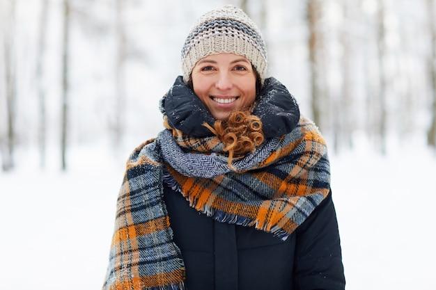 Улыбающаяся молодая женщина, наслаждаясь зимой