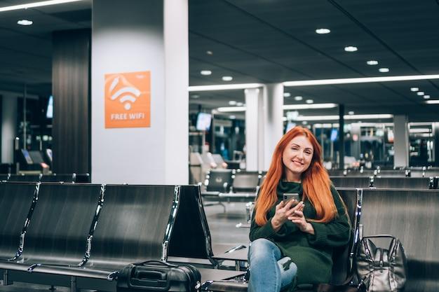 笑顔の若い女性は空港ターミナルで無料のwi-fiを楽しんでいます