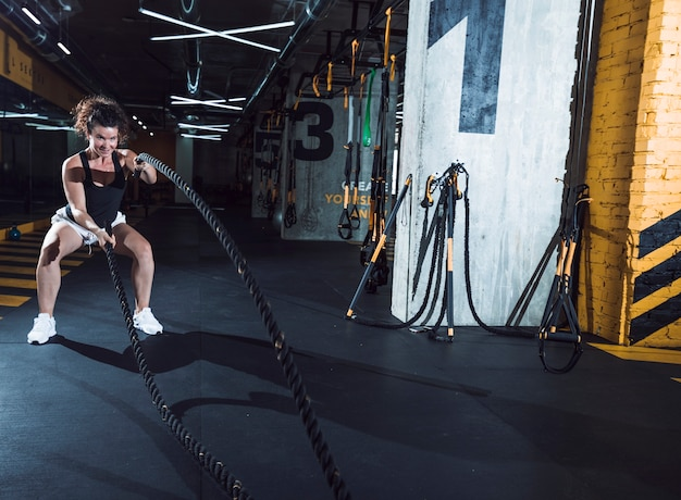 Smiling young woman exercising with battle ropes