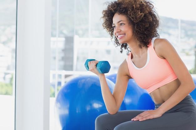 Улыбается молодая женщина, упражнения с гантель в тренажерном зале