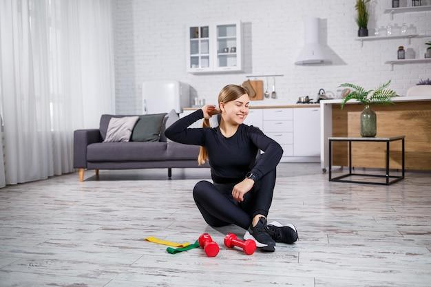 Улыбается молодая женщина упражнения с резинкой дома фитнес-тренировки. концепция здорового образа жизни. спорт дома во время карантина