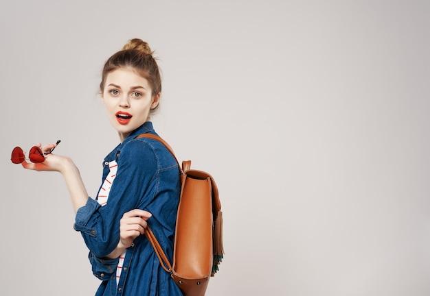 笑顔の若い女性のファッション服バックパック学生大学