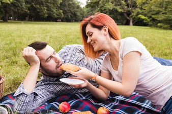 Smiling young woman feeding puff pastry to her boyfriend in the picnic