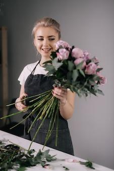 흰색 바탕에 꽃다발을 들고 앞치마를 입고 웃는 젊은 여성 꽃집