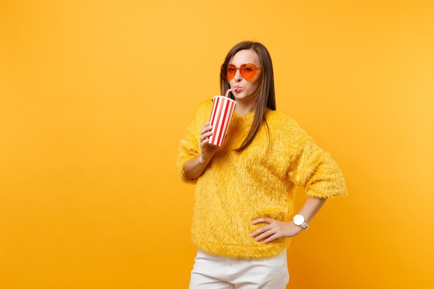 Smiling young woman in fur sweater and heart orange glasses drinking cola or soda from plastic cup isolated on bright yellow background. people sincere emotions, lifestyle concept. advertising area.