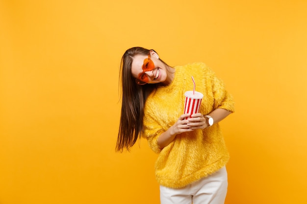 Smiling young woman in fur sweater and heart orange glasses holding plastic cup with cola or soda isolated on bright yellow background. people sincere emotions, lifestyle concept. advertising area.