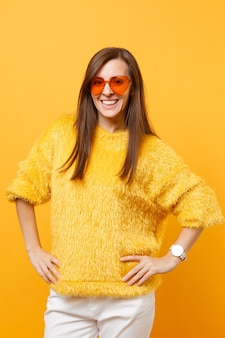Smiling young woman in fur sweater, white pants and heart orange glasses standing with arms akimbo isolated on bright yellow background. people sincere emotions, lifestyle concept. advertising area.
