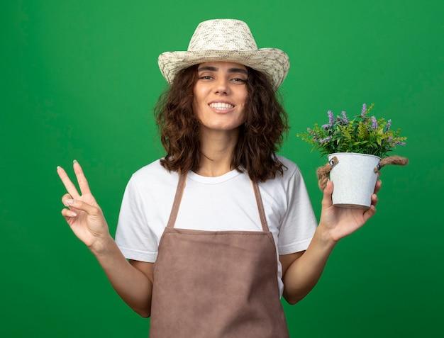 緑に分離された平和のジェスチャーを示す植木鉢に花を保持している園芸帽子を身に着けている制服を着た若い女性の庭師の笑顔