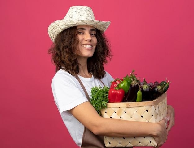 핑크에 고립 된 야채 바구니를 들고 원예 모자를 쓰고 제복을 입은 젊은 여자 정원사 미소