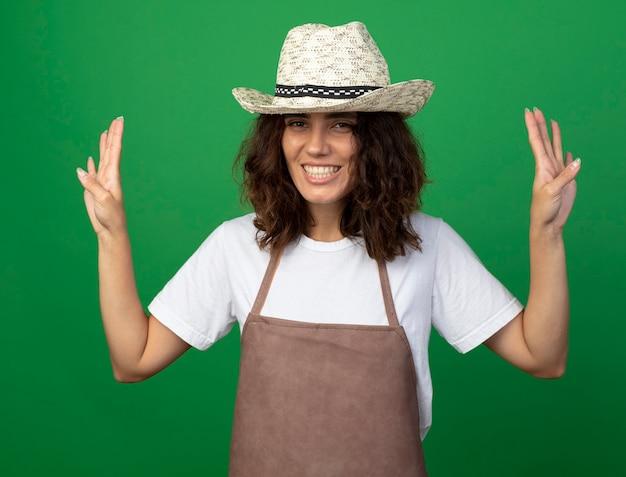 緑に分離された4つを示すガーデニング帽子を身に着けている制服を着た若い女性の庭師の笑顔