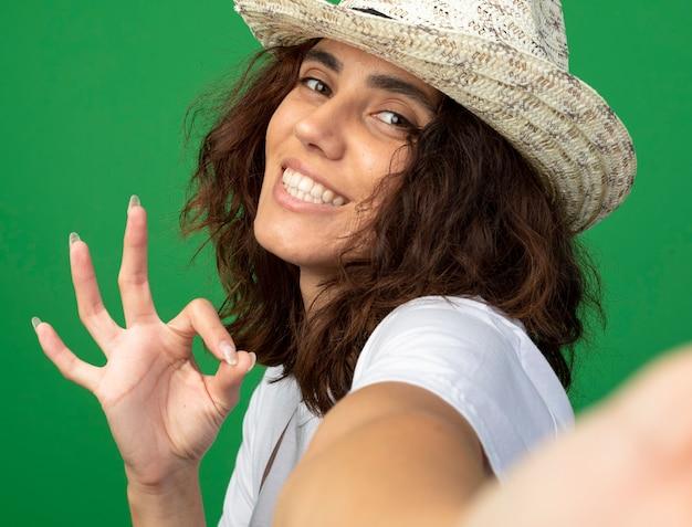 Giardiniere sorridente della giovane donna in uniforme che indossa la macchina fotografica della tenuta del cappello di giardinaggio che mostra gesto giusto isolato sul verde