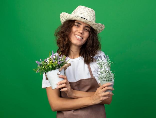 Giardiniere sorridente della giovane donna in uniforme che porta il cappello di giardinaggio che tiene e che attraversano i fiori in vasi da fiori isolati su verde