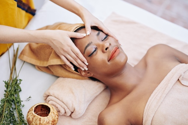 Smiling young woman getting relaxing rejuvenating face massage in spa salon, view from above