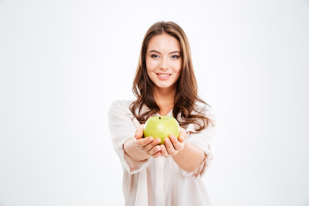Smiling young woman giving apple at front isolated on a white wall