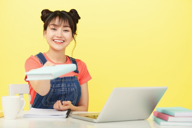 本を与える笑顔の若い女性