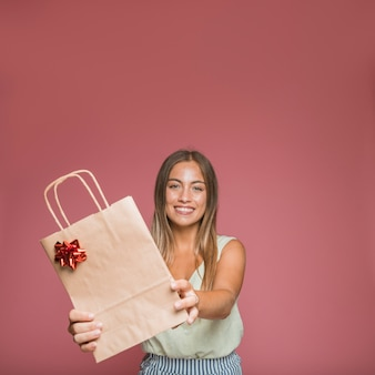 Smiling young woman giving paper shopping bag with red bow