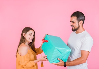 Smiling young woman giving taking gift from man against pink backdrop