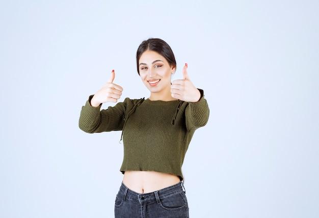 Улыбается молодая женщина, показывая пальцы вверх на белом фоне.