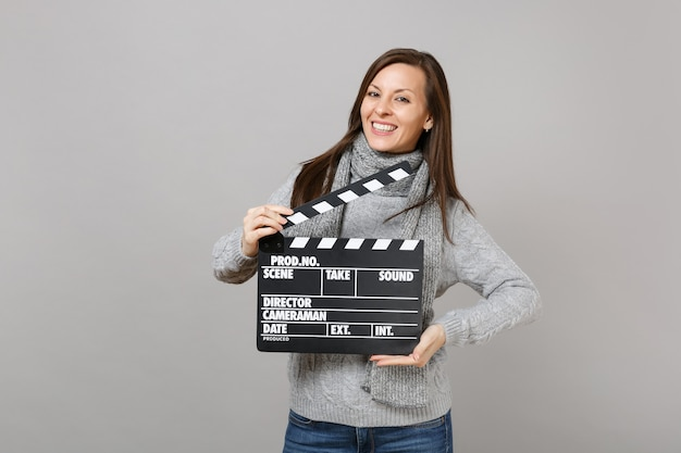 Smiling young woman in gray sweater, scarf hold classic black film making clapperboard isolated on grey background. healthy fashion lifestyle, people emotions, cold season concept. mock up copy space.