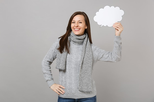 Smiling young woman in gray sweater, scarf holding empty blank say cloud, speech bubble isolated on grey background. healthy fashion lifestyle people emotions, cold season concept. mock up copy space.