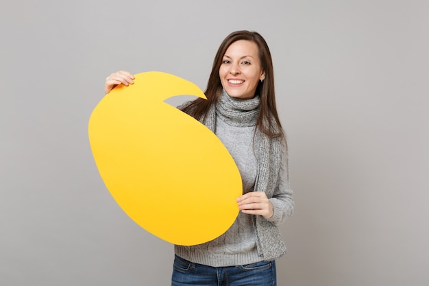 Smiling young woman in gray sweater, scarf holding yellow empty blank say cloud speech bubble isolated on grey wall background. healthy fashion lifestyle, people sincere emotions, cold season concept.