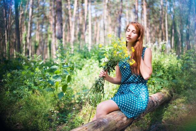 Smiling young woman in green dress sitting on log and holding yellow flowers in forest on sunny summer day.
